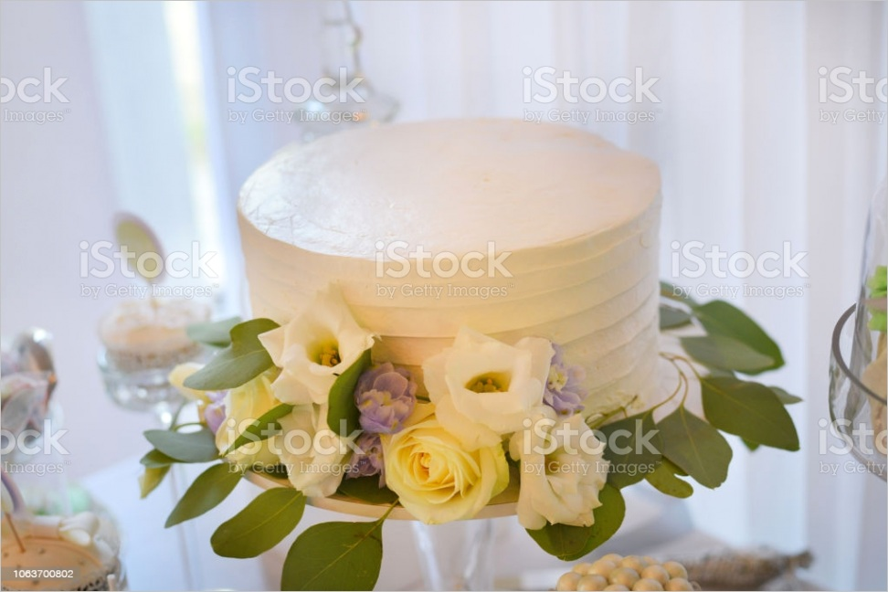 simple one layer white wedding cake decorated with flowers gm